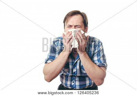 The man in a blue cough  shirt with a beard on cheeks cough in a snivel scarf.