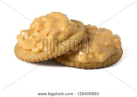Pimento Cheese spread on two Crackers isolated on white.