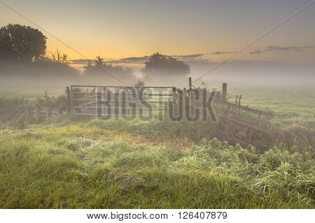 Gate And Fences In Foggy Farmland
