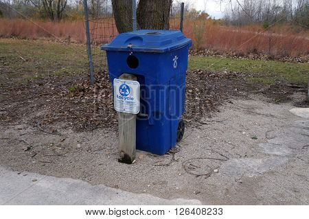 PLAINFIELD, ILLINOIS / UNITED STATES - OCTOBER 24, 2015: The Lake Renwick Heron Rookery Nature Preserve provides a blue bin where visitors may deposit recyclable aluminum, tin, plastic and glass.