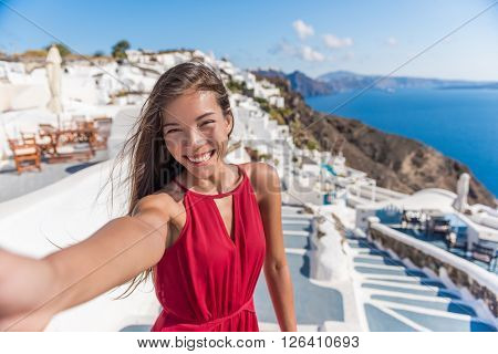 Travel Vacation Tourist Selfie. Woman taking self-portrait photo on Santorini, Greek Islands, Greece, Europe. Girl on summer vacation visiting famous tourist destination having fun smiling in Oia.