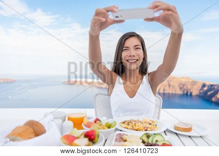 Woman taking photo of breakfast using mobile cell smart phone app. Girl taking pictures of food on luxury travel vacation for social media. Beautiful female in resort in Santorini, Greece, Europe.