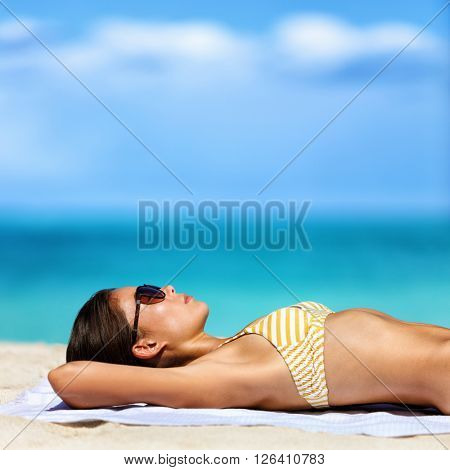 Beach vacation woman in bikini wearing sunglasses. Young lady sunbathing relaxing. Sexy young adult wearing eyewear for sun protection lying down on towel on sand tanning. Skincare UV sun care.
