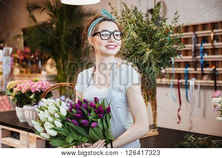 Cheerful attractive young woman florist holding white and purple tulips in flower shop