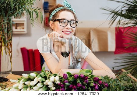 Portrait of attractive smiling young woman florist in glasses working in flower shop