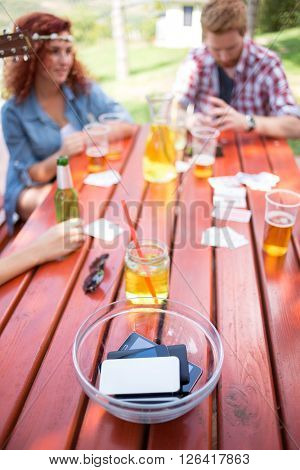 Youth postponed their mobile phones in glass bowl on wooden table outdoor