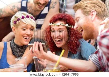 Curly ginger girl is delighted with photos on fellows mobile phone in restaurant in open