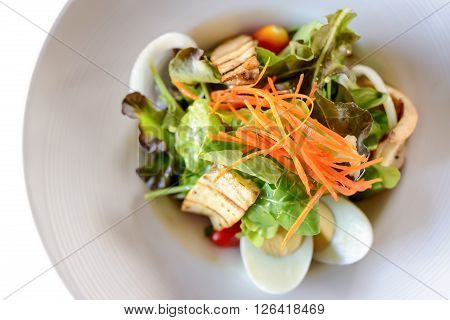 Delicious breakfast at the luxury hotel seafood salad on white plate. Isolated on white.