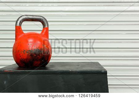 Red kettle bell on a black jump box, against a white roll-up door