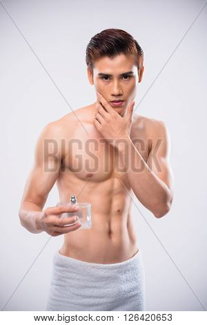 Attractive Vietnamese man applying aftershave on his skin