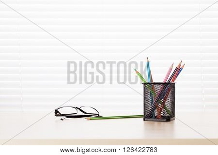 Office workplace with supplies on wood desk table in front of window with blinds. View with copy space
