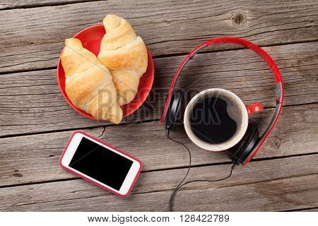 Fresh croissants, coffee, smartphone and headphones on wooden table
