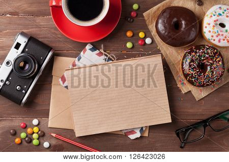 Notepad, donuts and coffee on wooden table. Top view with copy space