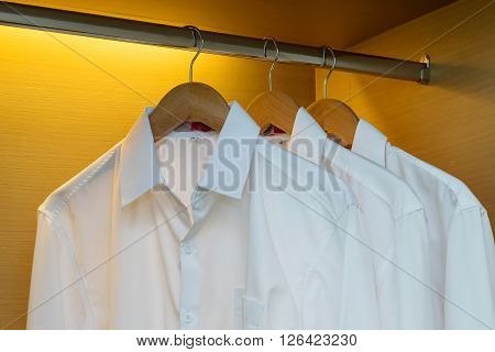 Row Of Shirts Hanging On Coat Hanger In Wooden Wardrobe