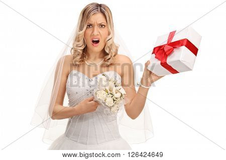 Young displeased bride holding a small wedding present isolated on white background