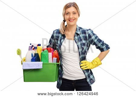 Cheerful blond housewife holding a bunch of cleaning products and looking at the camera isolated on white background