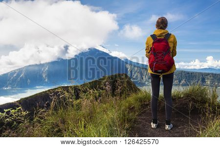 Lady hiker with rucksack looking at the volcano