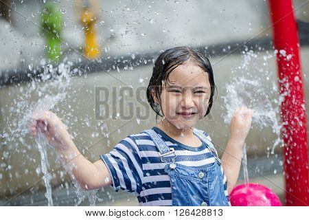 Asian girl playing with water fountain at water park