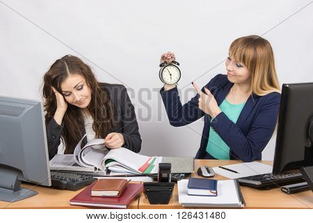 Two Girls In The Office Awaiting The End Of The Day And Look At The Clock