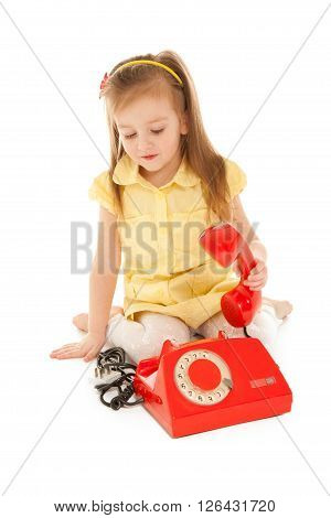 Little girl with old red phone sitting on the floor isolated