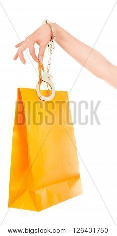 Woman hand with orange shopping bags and handcuffs isolated on white