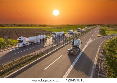 Many white gasoline tanker trucks in line and one without trailer driving towards the sun. Fast blurred motion drive on the freeway at beautiful sunset. Freight scene on the motorway near Belgrade Serbia.