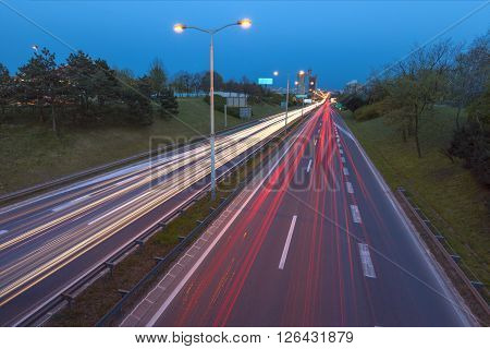Speed drive on freeway at the entrance to Belgrade Serbia with a view to the West Towers in the background. Llight trails at rush hour on motorway in long exposure shot.