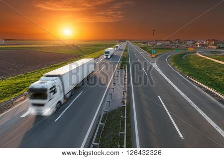 Many white trucks in line driving towards the sun. Fast blurred motion drive on the freeway at beautiful sunset. Freight scene on the motorway near Belgrade Serbia.