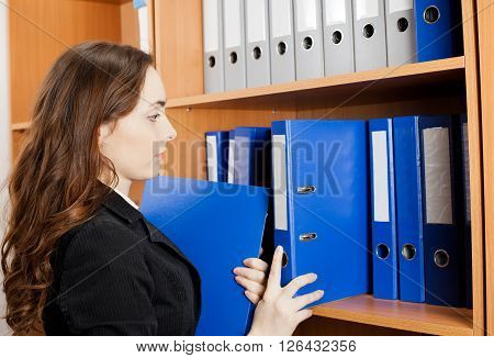 Beautiful woman taking a blue folder from shelf