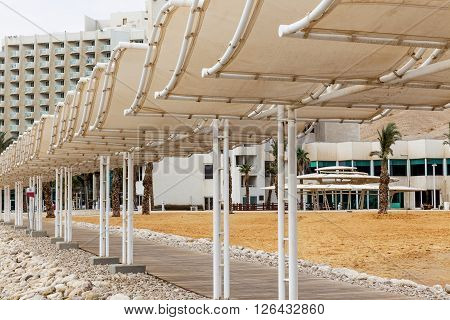 Wooden dock and sunshades on white hotel and yellow sand background