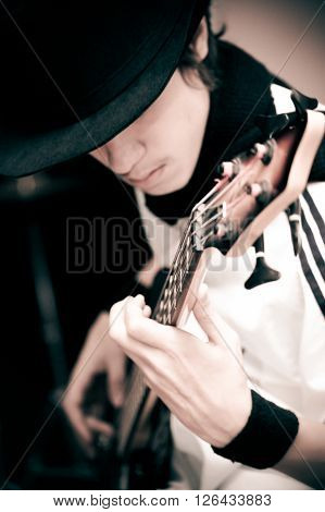 Young man in black hat with electric guitar