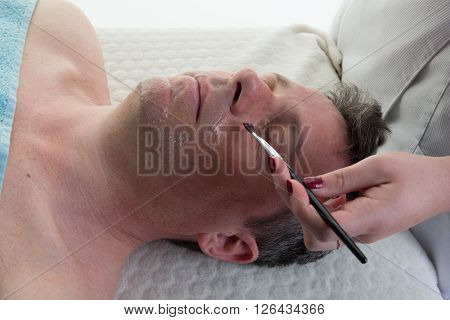 Hand Of Beautician Applying Cream On Male Face
