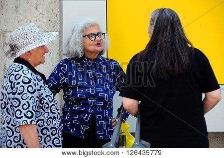 TRYAVNA, BULGARIA - JULY 6, 2015: Three elderly Caucasian women talk in the street of the town