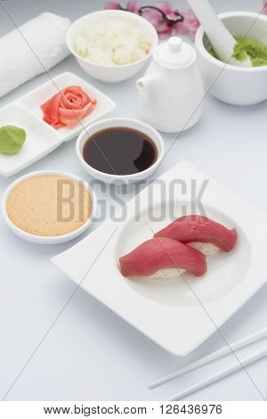 Tuna Sushi Nigiri With Ginger Wasabi And Soy Sauce On A White Plate