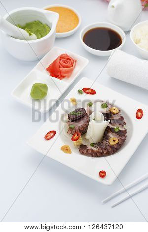 Salad With Octopus On A White Plate With Ginger Wasabi And Sauces.