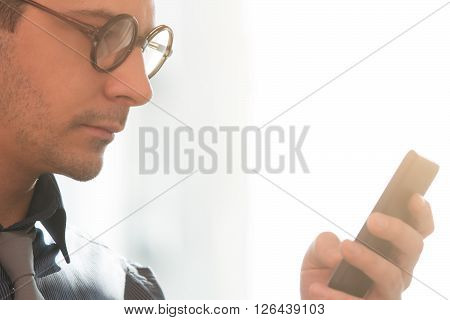 Businessman with eyeglasses typing messages on his smartphone.