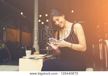 Attractive female student is reading laughable article in network on mobile phone while is sitting in university cafe. Woman chatting with her friends by cell telephone during breakfast in coffe shop