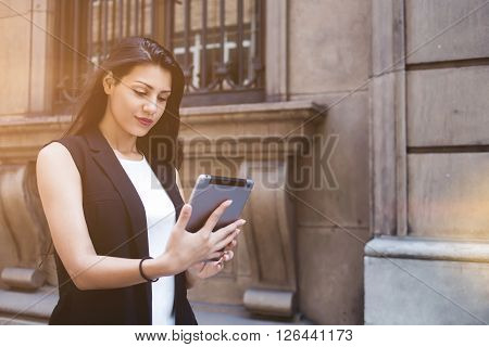 Lost female tourist is using digital tablet for navigation while is walking in urban setting during summer holidays latin woman wanderer viewing photos that she took on her touch pad during strolling