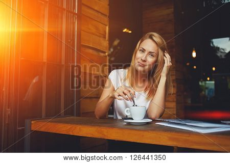 Young charming woman posing while sitting in cafe during coffee break attractive European female enjoying rest during recreation time beautiful lady relaxing in bar after walking in the fresh air