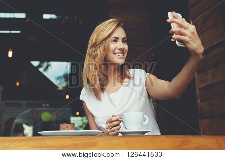 Happy smiling hipster girl making self portrait with mobile phone camera while sitting in modern coffee shop cheerful woman posing while photographing herself for social network picture copy space