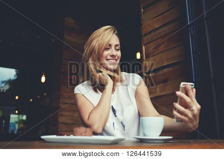 Young cheerful woman posing while photographing herself on smart phone camera for a chat with her friends attractive smiling hipster girl making self portrait on cell telephone while sitting in cafe