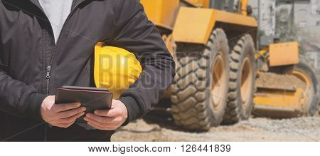 Construction engineer making notes on a tablet.