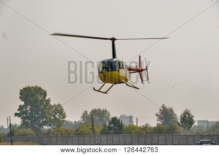 Tyumen, Russia - August 11, 2012: On a visit at UTair airshow in heliport Plehanovo. Pilot of Robinson R44 Raven shows flying opportunities