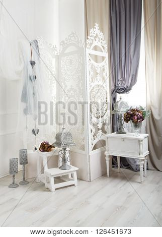 shabby chic room interior. Wedding decor, room decorated for shabby chic rustic wedding, with bedside table, folding screen or room divider with white tracery and rose bouquets. High key