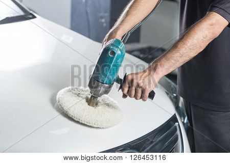 Car detailing series : Worker polishing white car