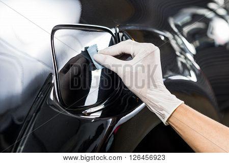 Car detailing series : Closeup of hand  coating car paint