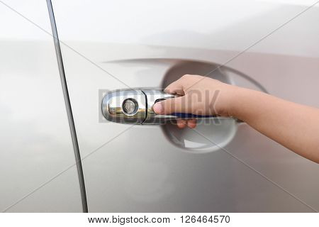 Hand boy pushing button of car handle to open car