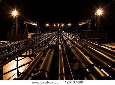 Night view of oil tanker deck view from fore to aft.