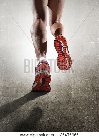 rear view close up strong athletic female legs and running shoes of sport woman jogging on grunge road in fitness healthy lifestyle high performance and endurance concept advertising style