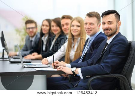 Confident businessman looking at camera among colleagues